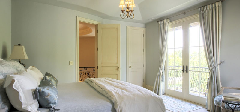 A bedroom with windows and doors