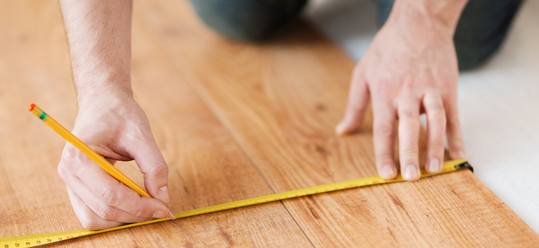 Close up of a man's hand measuring flooring panels