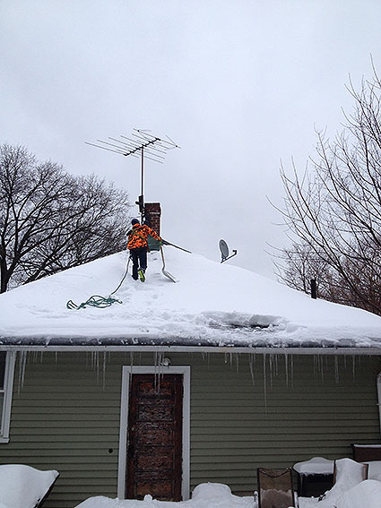 Removal of snow on a residential home roof top.